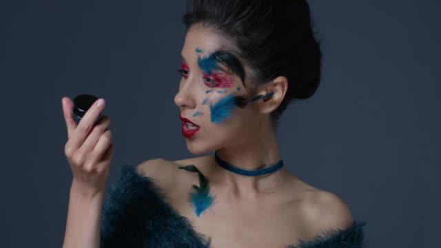 明るい舞台メイクと羽でブルネットのファッションモデルは、アイシャドウ jar ファイルを保持しています。ファッションのビデオ。 - グリースペイント点の映像素材/bロール