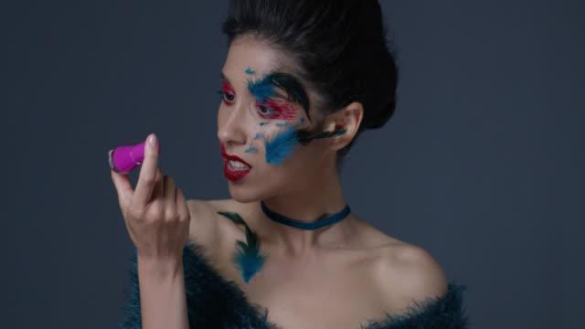 明るい舞台メイクと羽でブルネットのファッションモデルは、マニキュア液ボトルを保持しています。ファッションのビデオ。 - グリースペイント点の映像素材/bロール