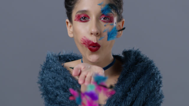 brunette fashion model in stage make-up blows feather from her hand.  fashion video. - clavicola video stock e b–roll