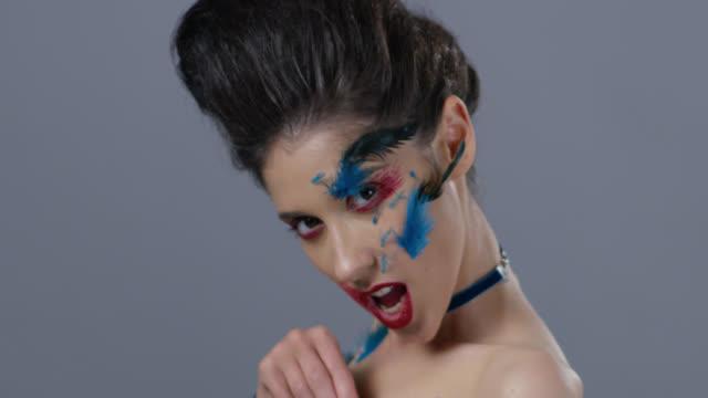 vidéos et rushes de brune mannequin dans le maquillage de scène se transforme et plumes d'autruche bleu montre, siffle. mode vidéo. - crayon à lèvres