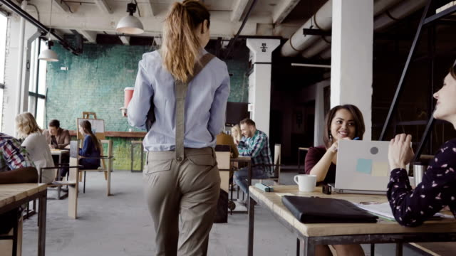 brunette female manager comes to modern office at work. young woman greets with colleagues, brings coffee to friend - arrivo video stock e b–roll