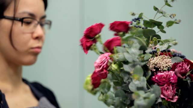 Brunette florist makes bouquet flower composition inside video