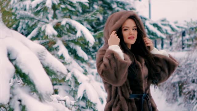 brunette girl in brown fur coat brushes walking in winter time slow motion video