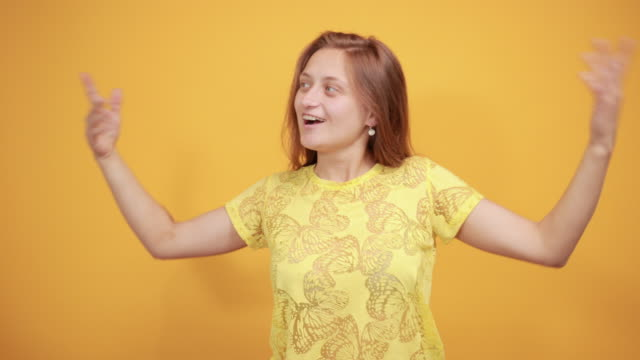 brunette girl in yellow t-shirt over isolated orange background shows emotions young beautiful brunette girl in yellow t-shirt over isolated orange background looking confident with smile on face, pointing oneself with fingers proud and happy vanity stock videos & royalty-free footage