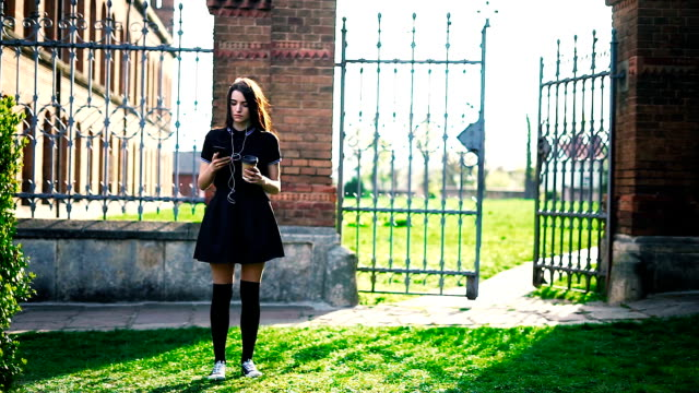 brunette girl listening music using white headphones with her smartphone on the background of university. Cinemagraph video