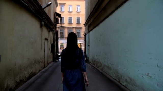 A brunette girl walking in a tunnel of buildings. Backview of a girl in a dark blue dress. Slow mo, steadicam shot video