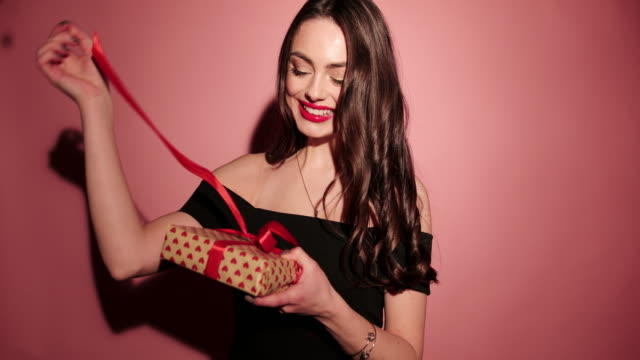 brunette happy woman open her present with confetti in pink background wear black dress - rosa rossa video stock e b–roll