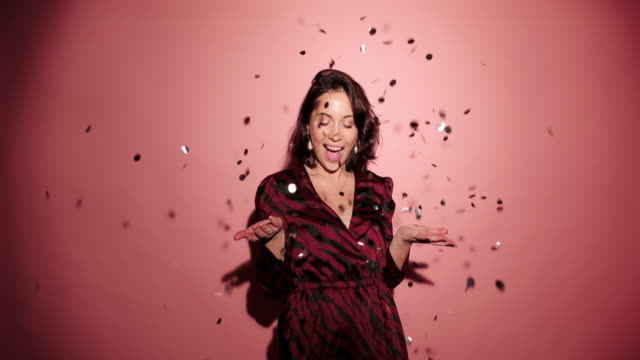 Brunette happy woman throw up and laugh to camera with confetti in pink background wear red dress