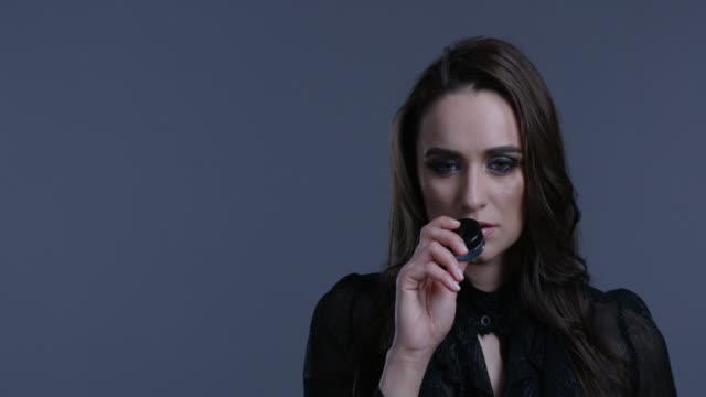 vidéos et rushes de brune mannequin de haut avec longs cheveux et maquillage lumineux détient pot de fard à paupières dans sa main. mode vidéo. - crayon à lèvres