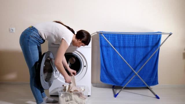 brünette dame hängt kleidung auf rack - waschmaschine wand stock-videos und b-roll-filmmaterial