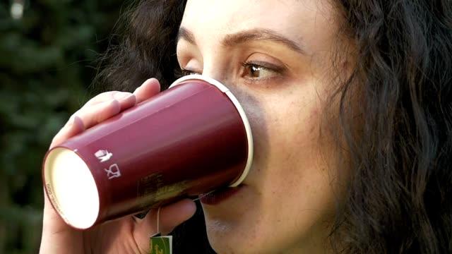 Brunette long hair girl portrait outdoors with tea video