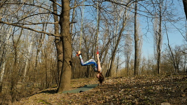 Brunette makes a aerogravity exercises on the ropes Young woman practicing aerogravity in the park. The woman makes physical exercises on the ropes on tree. Flexible female hanging on the ropes and stretching her body and muscles. She's moving slowly and accuracy. arthropod stock videos & royalty-free footage