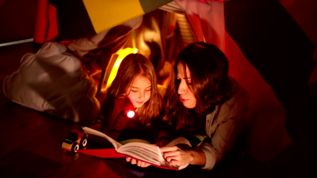 Brunette mother reading a fairy tale to her blond daughter video