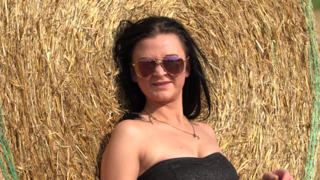 vídeos de stock e filmes b-roll de brunette on a beveled field near a bale of hay - flower white background