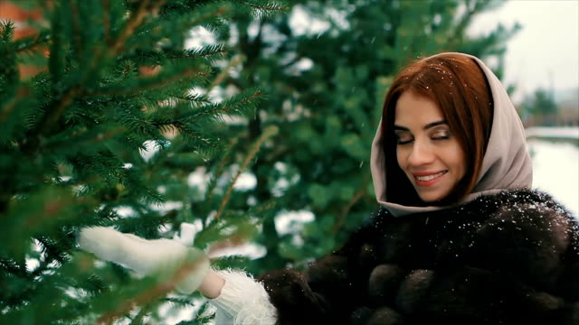 Brunette rich woman waist coat of brown fur near Christmas tree slow motion video