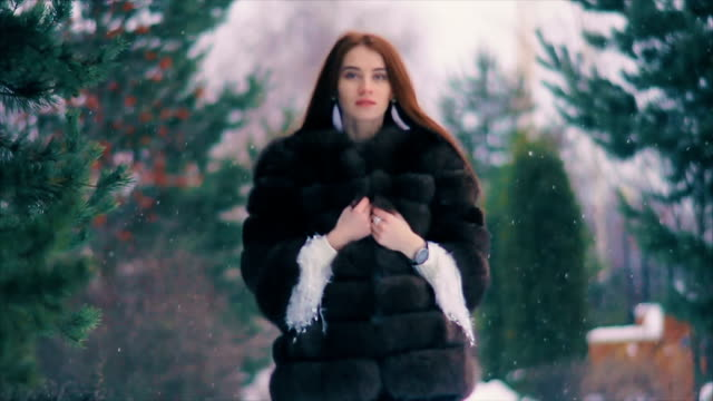 Brunette rich woman waist coat of brown fur on background of Christmas tree slow motion video