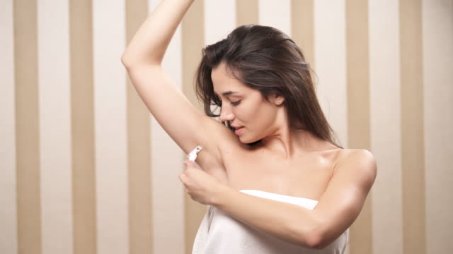 A brunette rolled up in a white towel holds a razor in left hand and shaves her right armpit video