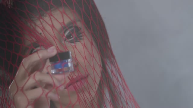 vídeos de stock e filmes b-roll de brunette sexy fashion model trapped in a red netting handles a blue eyeshadow jar. fashion video. - brilho labial