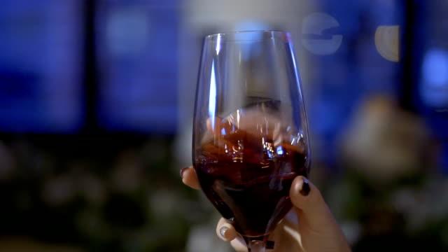 Brunette shakes wine in glass in slowmotion video