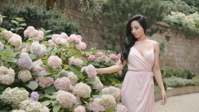 stockvideo's en b-roll-footage met brunette loopt door het steegje met bloemen. - hortensia