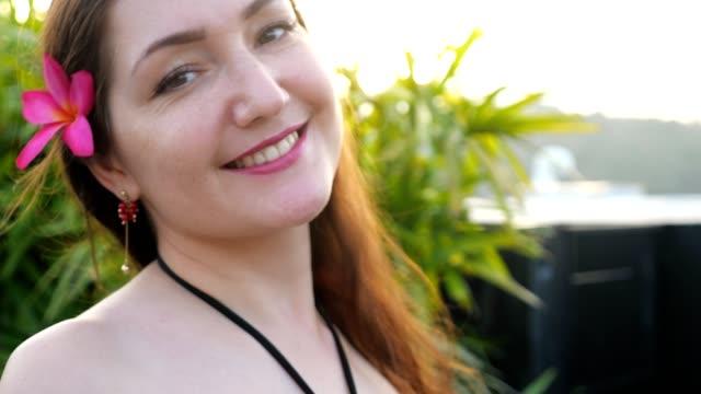vídeos de stock e filmes b-roll de brunette with flower in long loose hair poses with smile - puxar cabelos