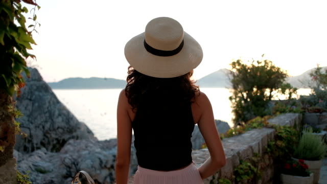 Brunette with luxurious curls and hat stand with back and look at sea video