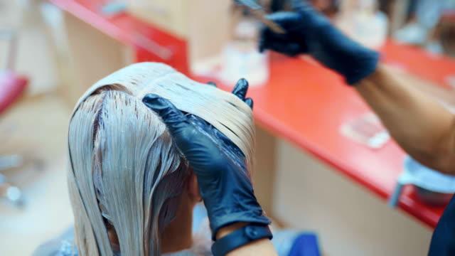 vídeos de stock e filmes b-roll de brunette woman dying her hair at the beauty salon - matéria corante