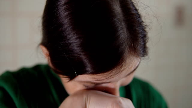 Brunette woman in a green sweater cries Brunette woman in a green sweater cries. onion stock videos & royalty-free footage