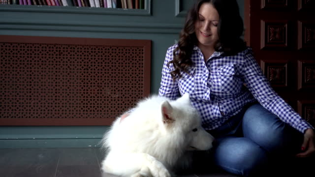 Brunette woman in checkered shirt is sitting with a pet dog on the floor video
