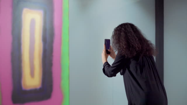 Brunette woman is taking photo of abstract picture in exhibit using smartphone - vídeo
