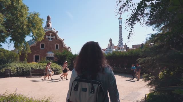 Brunette woman is walking in Park Guell area in sunny summer day, back view video
