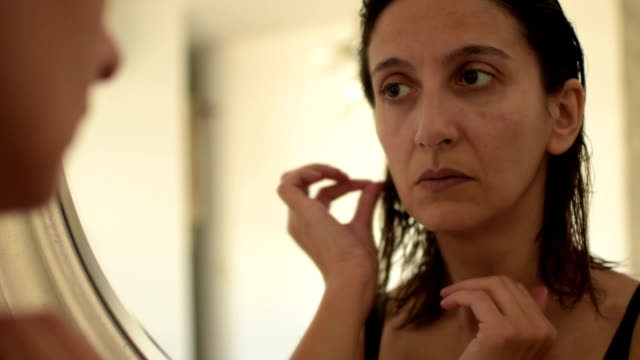 Brunette woman looking at skin in mirror video