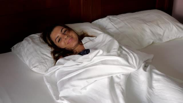 vídeos de stock e filmes b-roll de brunette woman lying in bed under the covers, pulls blanket having fun smiling - puxar cabelos