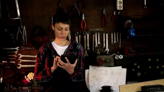 vidéos et rushes de femme brune, ingénieur en mécanique en regardant tablette en atelier - vidéos de rallonge électrique