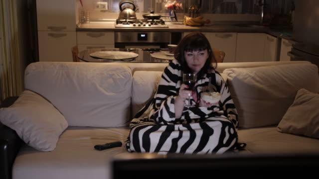 brunett kvinna koppla av på kvällen hemma på soffan med ett glas vin och glass tittar på tv - wine box bildbanksvideor och videomaterial från bakom kulisserna