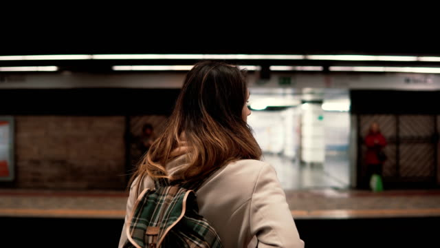 Brunette woman standing on railway station and waiting for her train. Girl in underground at evening looks on fast trams Brunette woman standing on the railway station and waiting for her train. Girl in underground at evening looks on the fast trams. Female with backpack moves around the city on a public transport. subway platform stock videos & royalty-free footage
