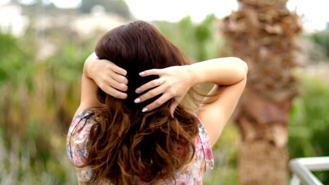 stockvideo's en b-roll-footage met brunette vrouw aanraken van haren. sensueel meisje haar waait. vrouw levensstijl - curly brown hair