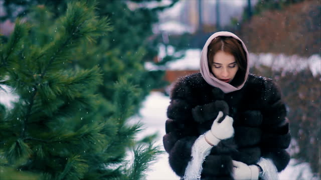 Brunette woman waist coat of brown fur in scarf walking slow motion video