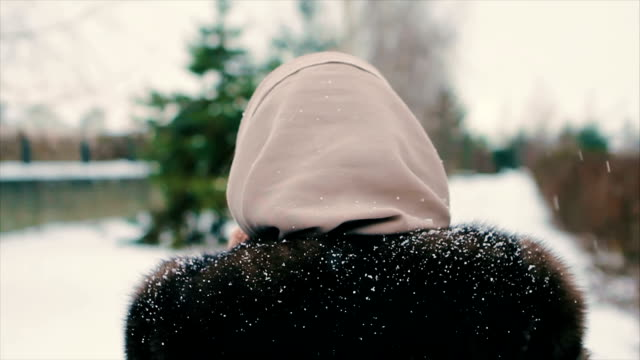 Brunette woman walking in snow park among christmas tree slow motion video