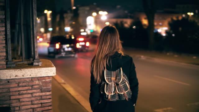 Mujer morena con mochila caminar tarde en la noche. Chica atractiva pasa por el centro de la ciudad cerca de la carretera en la noche - vídeo