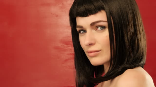 brunette woman with bob hair looking at camera on red background 02 - video