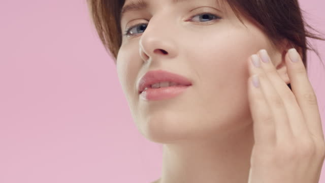 brunette woman with smooth healthy skin gently strokes her face - viziarsi video stock e b–roll