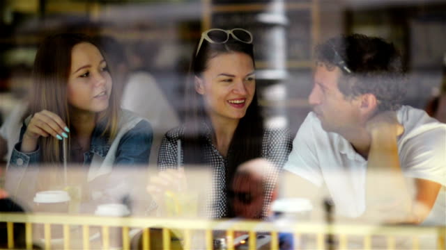 Brunette Woman with Two Friends Sitting at a Cafe, Drinking Some Beverages and Talking. Three Friends are Seen Through the Window of Restaurant video