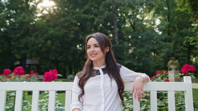 Brunnette Lady Sitting on White Bench in the Park video