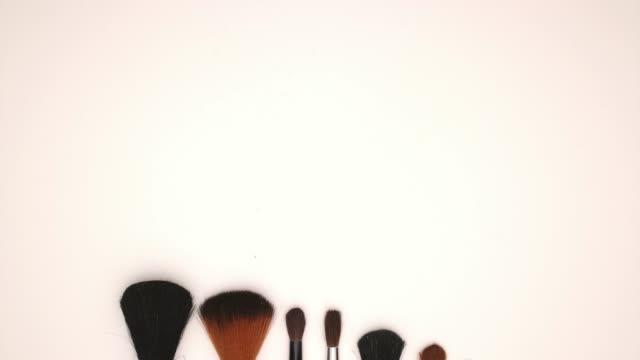 vidéos et rushes de outils de pinceau et d'ombre à paupières sur fond blanc-stop moton - pinceau à maquillage