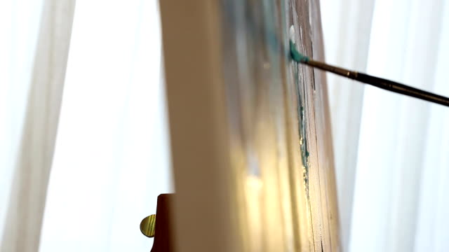 brush close-up, which draw a picture. sunlight shines from the window, and the shadow of the brush is reflected in the picture - tavolozza video stock e b–roll