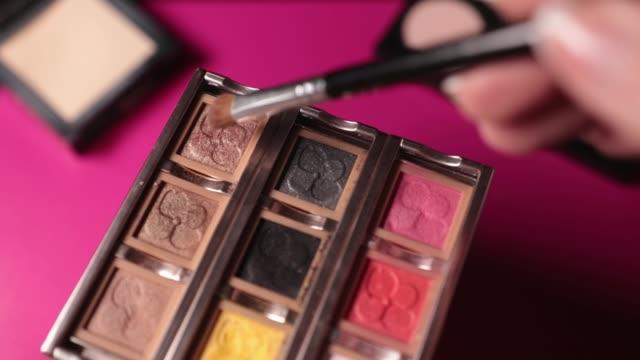 vídeos de stock e filmes b-roll de brush collect color eyes shadows for make-up on pink background. - sombra para os olhos