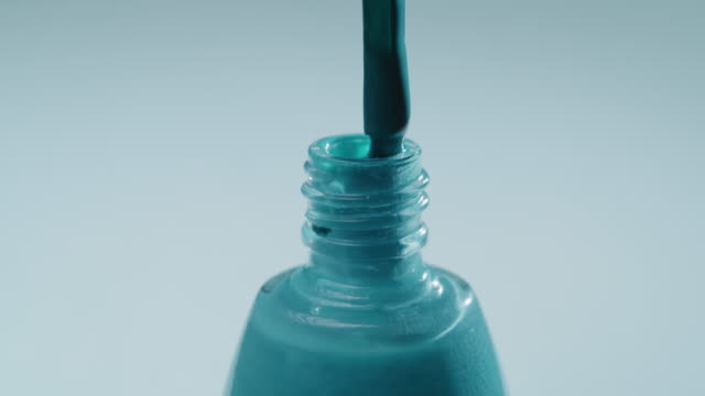 Brush is taking turquoise nail polish from the bottle. Extreme close-up