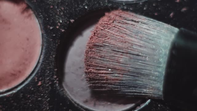 Brush tapped on gray shadow on make up pallet Brush tapped on gray shadow on black plastic make up pallet, macro close up eyeliner stock videos & royalty-free footage