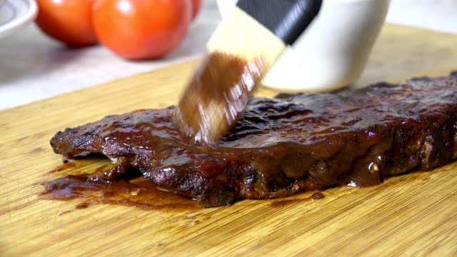 Brushing barbecue sauce on ribs